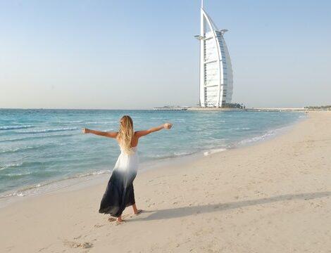 гледка към бурж ал араб и жена в гръб върви по плажа